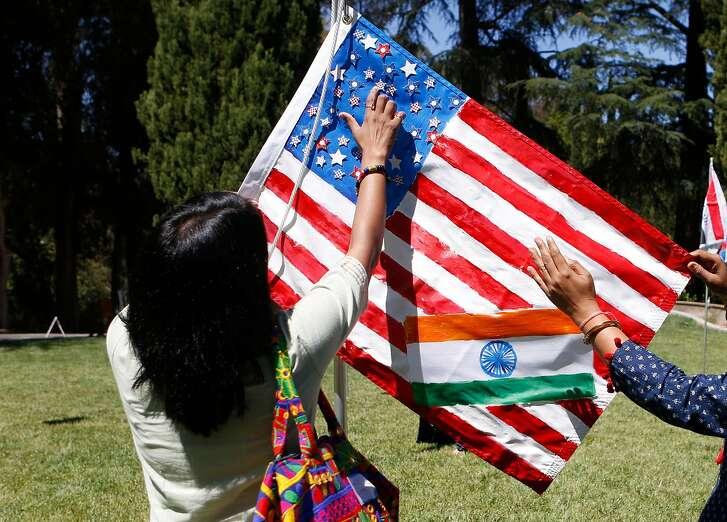Rakhi Surana, of Madhya Pradesh, India, and Ratnapriya Rai, of Bangalore India, finish decorating an American Indian flag collaboration for an outdoor installation by Brazilian artist Maril� Dardot called Saudade (Our Flags) at Montalvo on Sunday, July 15, 2018 in Saratoga, Calif.