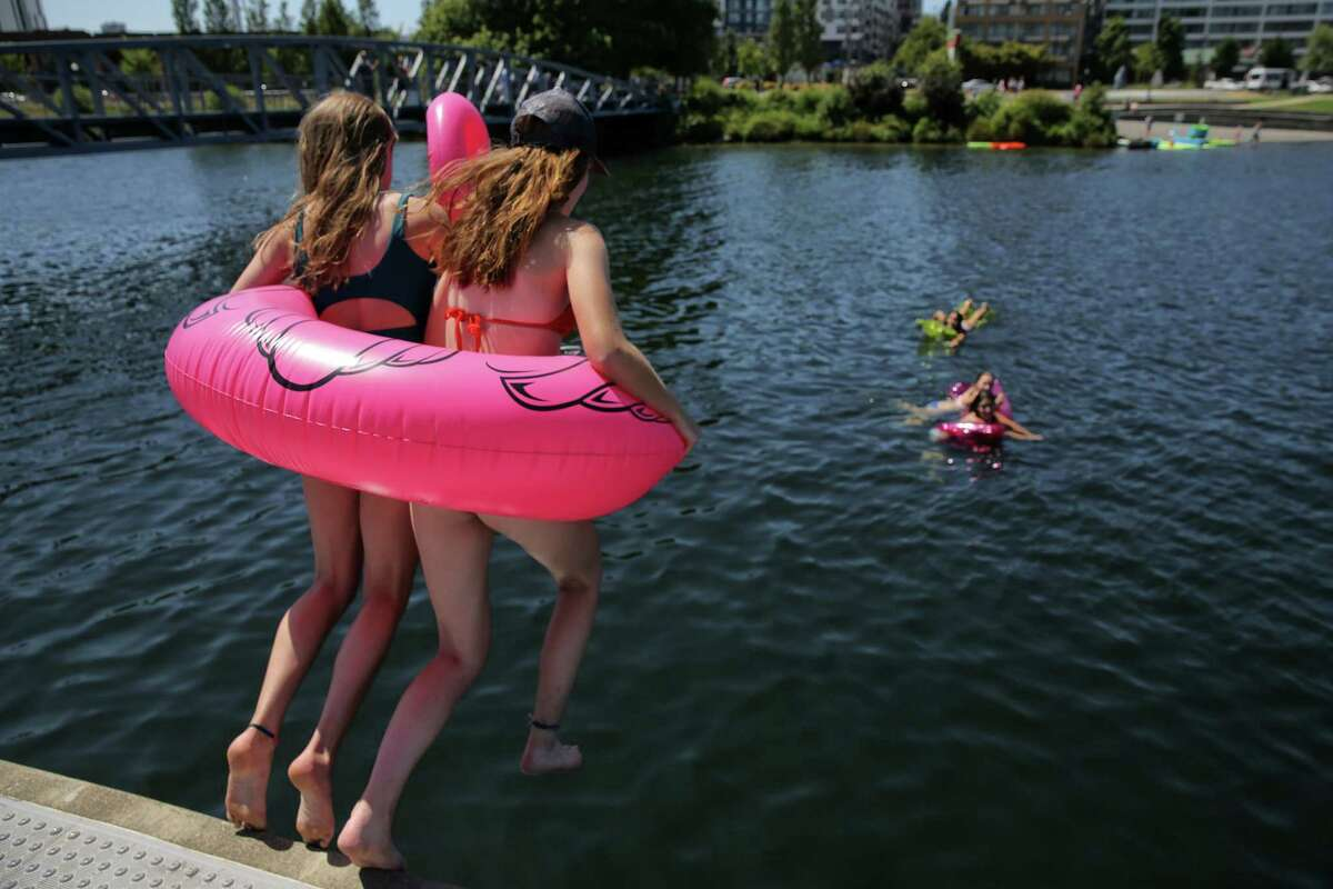 Seattleites beat the heat at South Lake Union Park as temperatures nearly reach 90 degrees, Monday, July 16, 2018.