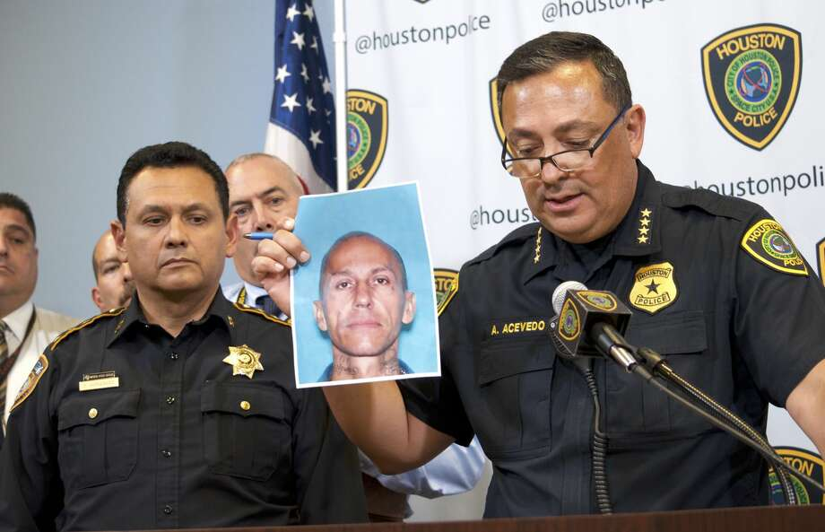 Houston Police Chief Art Acevedo, right, holds up a photo ofJose Gilberto Rodriguez, 46, as Harris County Sheriff Ed Gonzalez looks on Monday July 16, 2018. Rodriguez is accused in three separate killings and two other violent robberies. Photo: Jay R. Jordan