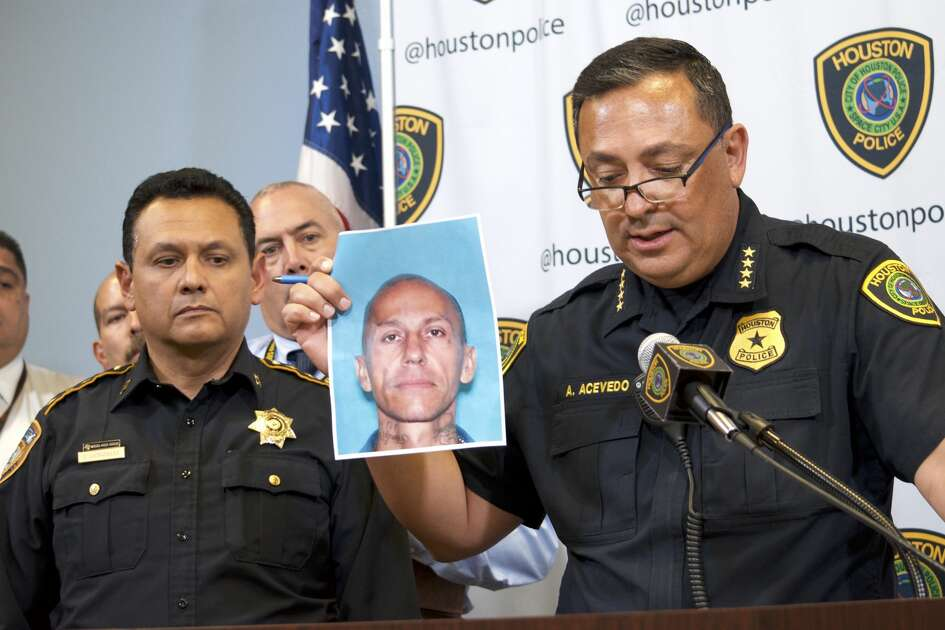 Houston Police Chief Art Acevedo, right, holds up a photo of Jose Gilberto Rodriguez, 46, as Harris County Sheriff Ed Gonzalez looks on Monday July 16, 2018. Rodriguez is accused in three separate killings and two other violent robberies.