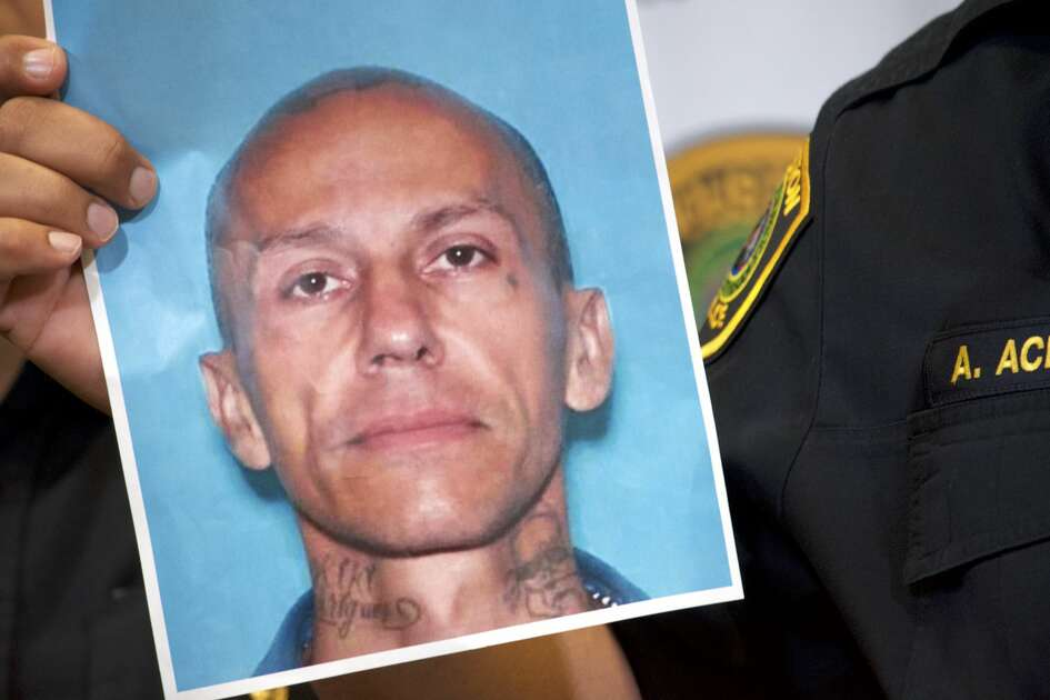 Houston Police Chief Art Acevedo holds up a photo ofJose Gilberto Rodriguez, 46, on Monday July 16, 2018. Rodriguez is accused in three separate killings and two other violent robberies.
