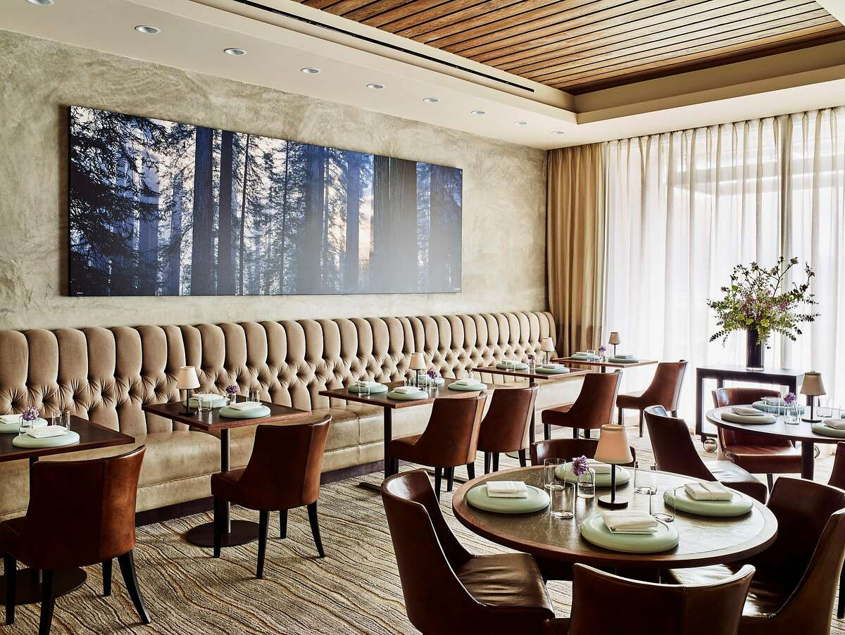 Protege restaurant's interiors contain warm walnut woods, and in the formal dining room, seen here, a carpet done ina faux bois pattern. Tables throughout the restaurant, including the cafe, are made of solid cross-cut walnut butcher block, some 2 inches thick.