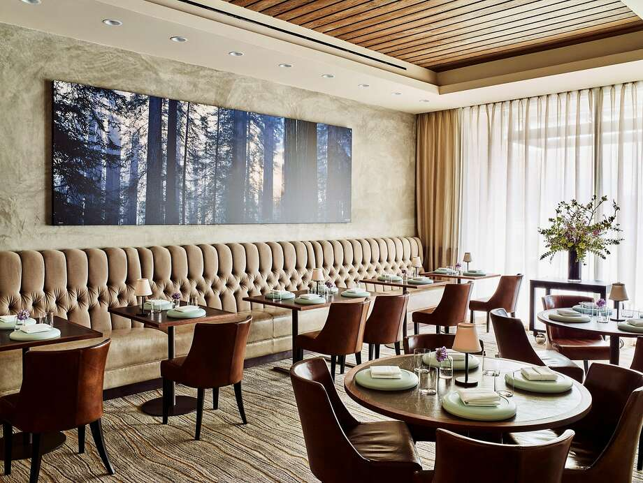 "Protégé restaurant's interiors contain warm walnut woods. In the formal dining room, seen here, a carpet exhibits a faux bois pattern. Many tables are made of solid cross-cut walnut butcher block, some 2 inches thick. The intention was to make it feel ""clubby"" but not stuffy for diners eating in the lounge or in the restaurant. ""To solve their design, I looked to their food — it's casual, comforting and familiar, but it's also super refined and super well-thought-out,"" said designer Jon de la Cruz. Photo: Douglas Friedman"