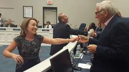 New Judson Superintendent Jeanette Ball, left, shakes hands with trustee Richard LaFoille on Monday. Her husband, Joe Reyes, center, joined her in greeting the board members following their unanimous decision.