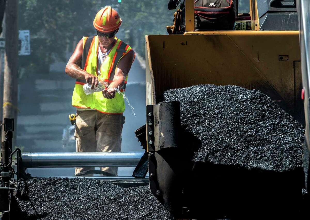 One of the members of the New Castle Paving Company douses himself with water in the 90+ degree heat and high due point humidity during the paving of Lark Street Monday, July 16, 2018 in Albany, N.Y. (Skip Dickstein/Times Union)