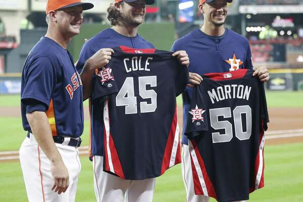 A.J. Hinch gives Gerrit Cole (45) and Charlie Morton their All-Star jerseys.