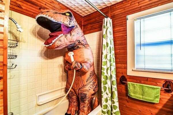 A real estate agent selling this two-bedroom, one-bathroom lake house in Granbury, TX, has hired an extra straight from the Cretaceous era to help out with the listing photos: a giant T. Rex.