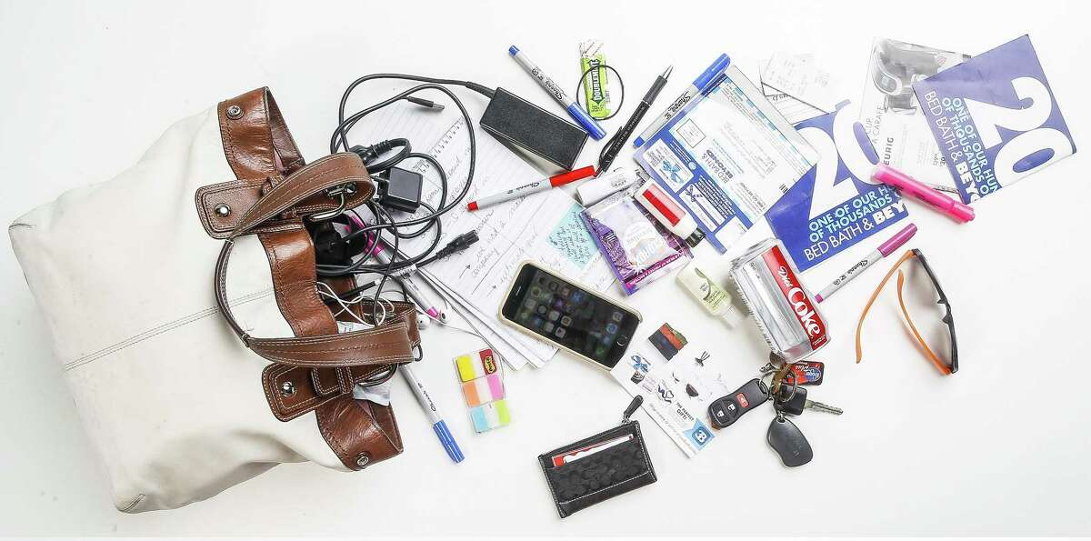 Reporter Maggie Gordon shows off the contents of her purse after going through a no purse week July 10, 2018 in Houston. (Michael Ciaglo / Houston Chronicle)