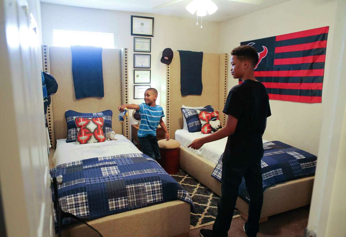 Arica Bibbs' sons explore their newly furnished and re-designed room in their apartment after a makeover from the Houston chapter of Dwell with Dignity.