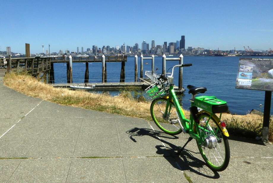 An electric LimeBike parked near the water with downtown Seattle in the distance. Photo: Pam Mandel / Special To The Chronicle