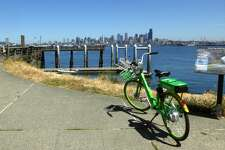 An electric LimeBike parked near the water with downtown Seattle in the distance.