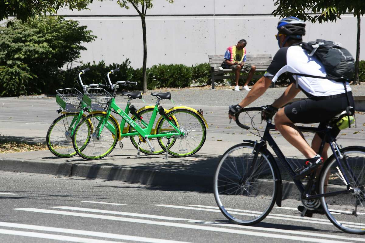 LimeBike, one of two new dock-less bike share programs, has placed bikes for public use around the city, including these two in lower Queen Anne, July 26, 2017. Bikes are unlocked via an app and do not come with helmets. (Genna Martin, seattlepi.com)