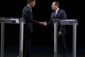 Democratic candidates for governor Ned Lamont, left, and Bridgeport Mayor Joe Ganim shake hands at the end of debate in New Haven, Conn., Thursday, July 12, 2018. Lamont is the party's endorsed candidate, while Ganim petitioned his way onto the Aug. 14 ballot. (AP Photo/Jessica Hill)