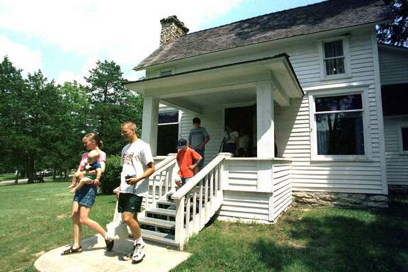 FOR IMMEDIATE RELEASE--Visitors exit the Laura Ingalls Wilder home in Mansfield, Mo., Aug. 4, 2000, following a tour of the homestead. Last year, nearly 50,000 people toured the home and museum, which is on the National Registry of Historical Places. (AP Photo/John S. Stewart)