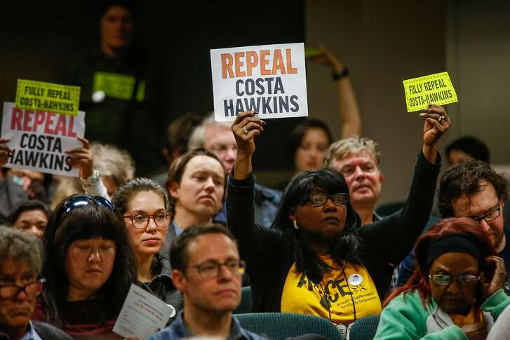 People hold up signs during a hearing to decide whether or not to repeal the Costa Hawkins Rental Housing Act at the State Capital in Sacramento, Calif., on Thursday, Jan. 11, 2018.  The Costa Hawkins Rental Housing Act did not pass.