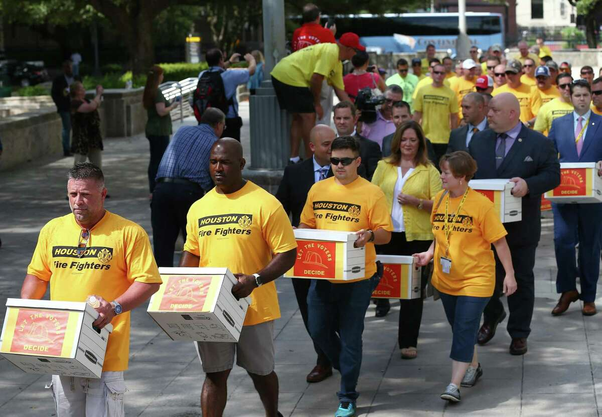 Houston firefighters carry boxes, filled with more than 32,000 signatures to put equal pay on the ballot, over to the City Hall Annex building Monday, July 17, 2017, in Houston. ( Godofredo A. Vasquez / Houston Chronicle )