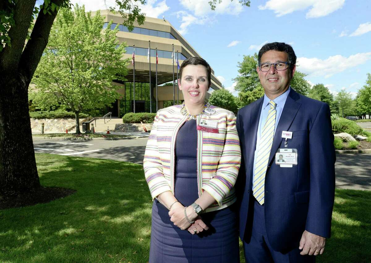 Liz Longmore and Dr. Rod Acosta, two of the executives of Stamford Health Medical Group, are photographed on July 12, 2018, in front of 1 Omega Drive, in the River Bend office complex, in Stamford, Conn. Stamford Health Medical Group will be relocating its administrative offices in September to 1 Omega Drive.