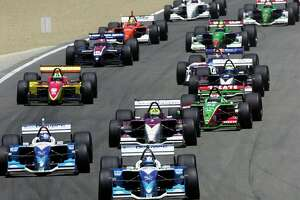 Patrick Carpentier, bottom, leads the field into the hairpin during CART's Grand Prix of Monterey at Laguna Seca Raceway in Monterey, Calif., on Sunday, June 15, 2003. Carpentier won the race; Bruno Junqueira of Brazil, directly behind Carpentier, was second. Paul Tracy, left front, was third. (AP Photo/Marcio Jose Sanchez)
