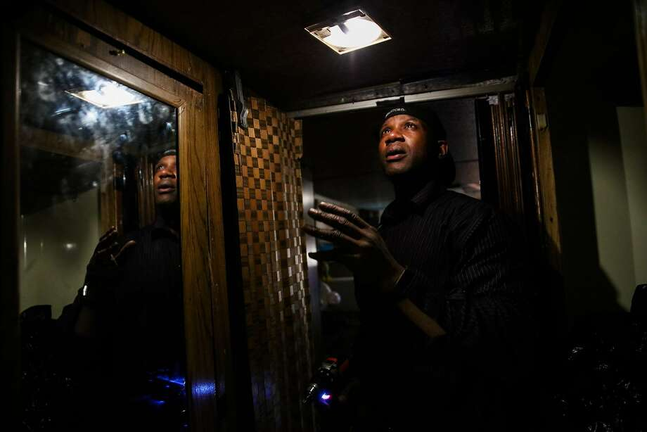 Arnell Clark fixes a light fixture in his RV in East Palo Alto. Photo: Gabrielle Lurie / The Chronicle