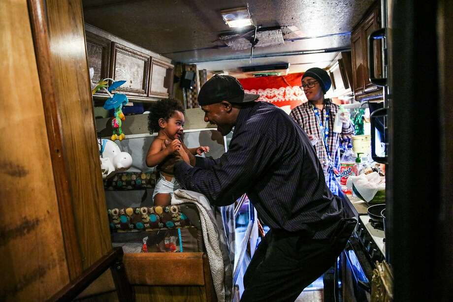 Arnell Clark plays with son Arnez Clark while girlfriend Mataele Robertson readies formula in their RV in East Palo Alto. Photo: Gabrielle Lurie / The Chronicle