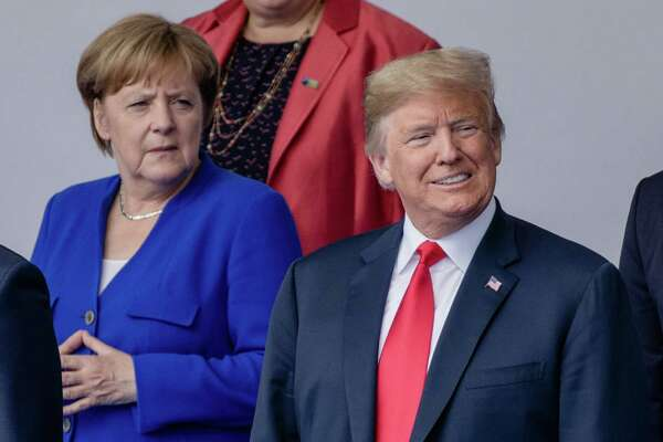 President Trump took a jab at German Chancellor Angela Merkel, left, saying that lax immigration policies have hurt her politically.