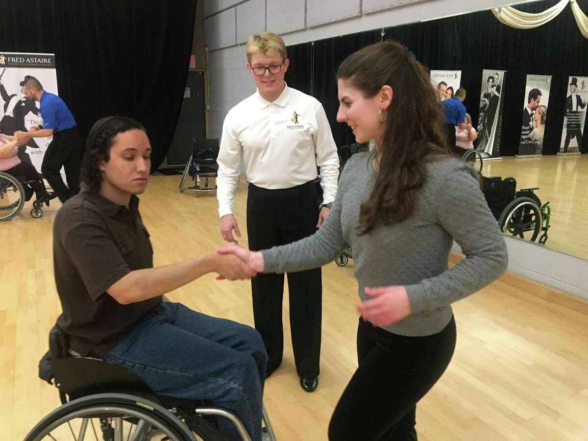 Mykhailo Annienkov, center, an instructor at Fred Astaire Bloomfield Hills in Michigan, watches Middletown instructor Annie Rockhill, center, lead Andrew Downs, left, a Fred Astaire Bloomfield Hills student, in a para dance session.