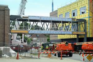 A new pedestrian bridge, spanning King Street, was set into place Friday between the old Stratford High School building, left, and the new expansion under construction to the right, in Stratford, Conn. June 8, 2018. The ongoing constriction at The Home of the Red Devils will move the District 2 polling place to Town Hall nearby for the August 14 primary.