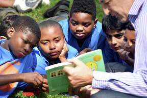 Charles Noble (right) of Hamden reads Smile during the LEAP Read-In on the Green in New Haven on July 13, 2018.