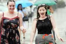 Greenwich residents, Jeanne Blin, left, and Ashleigh Gallagher, react as they were caught in the rain downpour on Greenwich Avenue during the thunder and lightning storm that hit Greenwich, Conn., Tuesday afternoon, July 17, 2018.