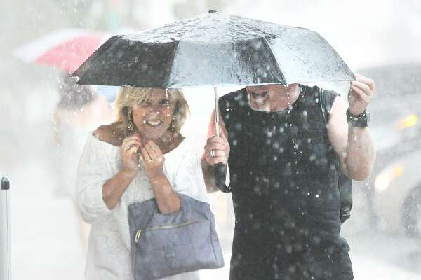 Melanie Campbell, left, and Hendrik Thijsen, both of Fairfield, used an umbrella while caught in the rain on Greenwich Avenue during the thunder and lightning storm that hit Greenwich, Conn., Tuesday afternoon, July 17, 2018.