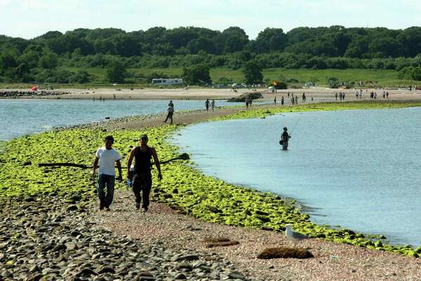 People traverse the tombolo, or sandbar, that leads to Charles Island at Silver Sands State Park in Milford, Conn., on Thursday July 12, 2018. Several new sign have been posted to warn people about the dangers of using the land bridge which is covered by the tides on a daily basis.