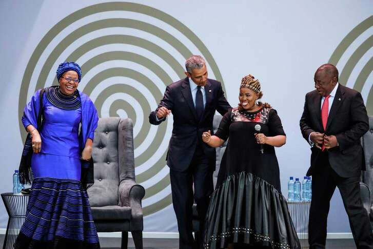 TOPSHOT - Former US President Barack Obama (2nd L), Graca Machel (L), widow of former South African president and global icon Nelson Mandela, and South African President Cyril Ramaphosa (R) dance as South-Africamn singer Thandiswa Mazwai (2nd R) performs during the 2018 Nelson Mandela Annual Lecture at the Wanderers cricket stadium in Johannesburg on July 17, 2018.  Former US president Barack Obama will deliver the Nelson Mandela Annual Lecture, urging young people to fight to defend democracy, human rights and peace, to a crowd of 15,000 people at the club as the centrepiece of celebrations marking 100 years since Nelson Mandela's birth. Obama has made relatively few public appearances since leaving the White House in 2017, but he has often credited Mandela for being one of the great inspirations in his life.   / AFP PHOTO / MARCO LONGARIMARCO LONGARI/AFP/Getty Images
