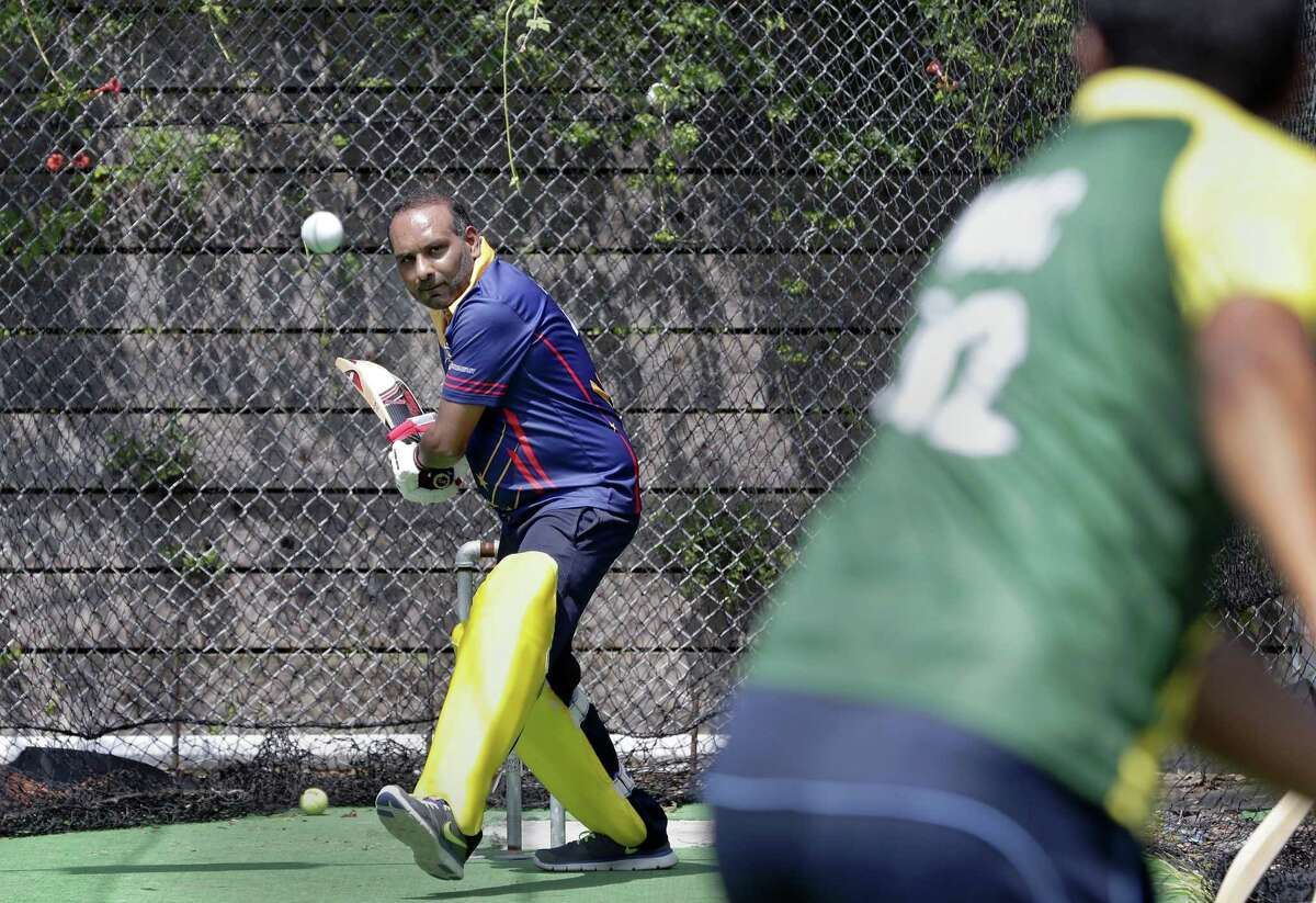 Tanweer Ahmed practices batting with some of his teammates inside his cricket batting cage next to the parking lot of his office June 22, 2018, in Houston, TX. (Michael Wyke / For the Chronicle)