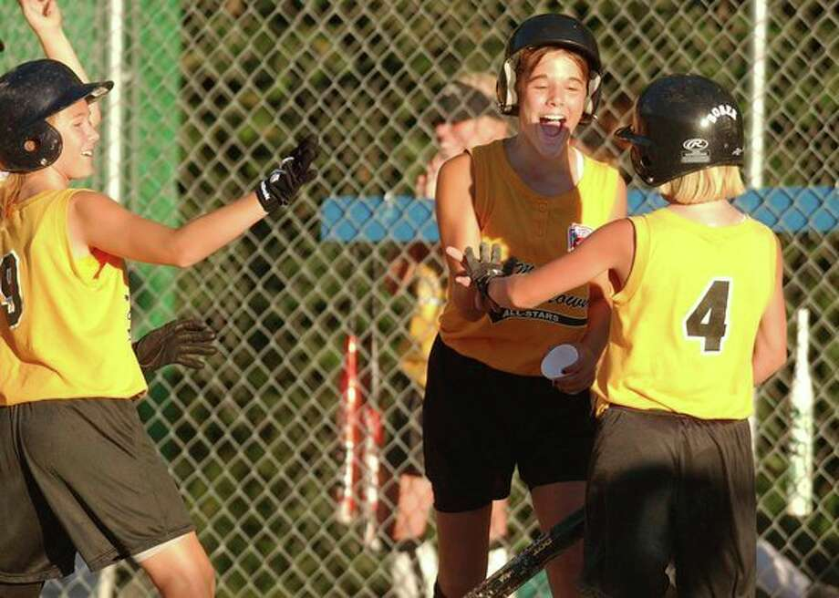 Jessica Chatterton (4) is greeted by Renae Lange after scoring for Southtown during the 2002 Little League Softball major state tournament in Bullock Creek. (Daily News file photo)