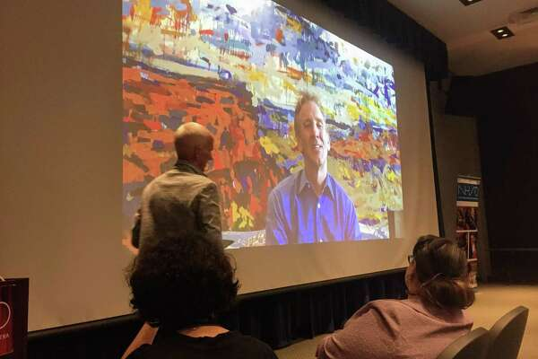 NHSO Board of Directors President Paul Hermes, left, introduces Neale, on screen, at SCSU.