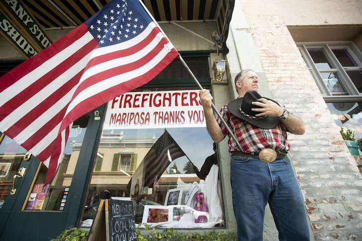 Charles Phillips waits for a procession carrying the body of firefighter Braden Varney on Monday, July 16, 2018, in Mariposa, Calif. Varney died Saturday while battling the Ferguson fire when his bulldozer overturned. (AP Photo/Noah Berger)
