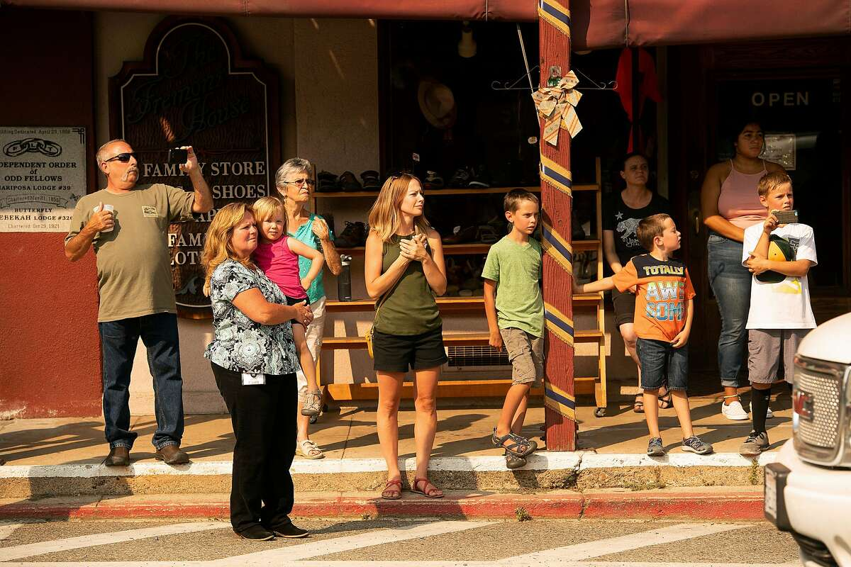Residents gather to watch a procession carrying the body of firefighter Braden Varney in Mariposa, Calif., on Monday, July 16, 2018. Varney died Saturday while battling the Ferguson fire when his bulldozer overturned. (AP Photo/Noah Berger)