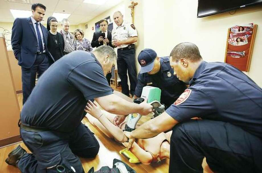In this August 2016 file photo, Alton firefighters demonstrate a new device called the Lucas 2, which provides the compressions to the chest of a full cardiac arrest patient as part of the CPR process. Alton firefighters Russell Long, left, John Bolling, center, and Capt. Wayne Harris, right, attach the device to a dummy as Mayor Brant Walker, Fire Chief Bernie Sebold and OSF St. Anthony's Hospital officials watch. The hospital donated nearly half of the money needed to purchase the life saving device. On Tuesday, it was announced that the fire department would receive a $227,000 grant, part of which will go toward a training vehicle. Photo:       John Badman | Telegraph File Photo
