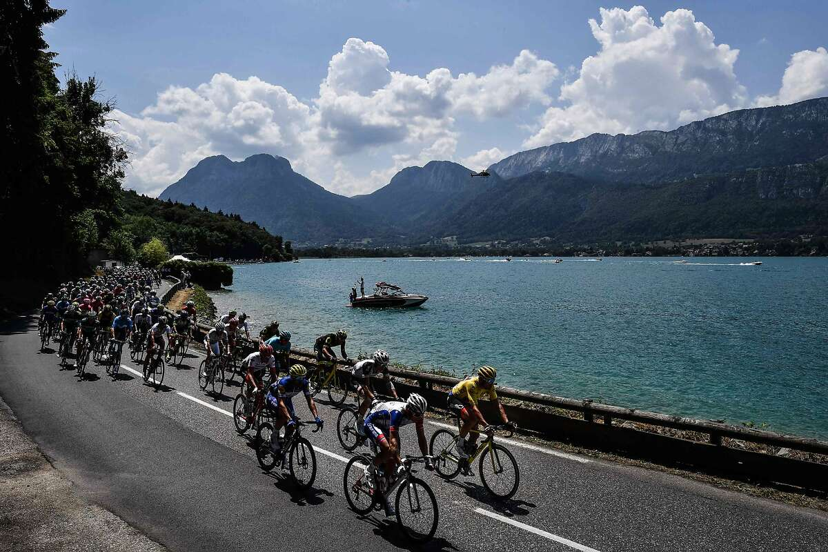 TOPSHOT - Belgium's Greg Van Avermaet (R), wearing the overall leader's yellow jersey, and the pack ride along the lake of Annecy during the tenth stage of the 105th edition of the Tour de France cycling race between Annecy and Le Grand-Bornand, French Alps, on July 17, 2018. / AFP PHOTO / Jeff PACHOUDJEFF PACHOUD/AFP/Getty Images