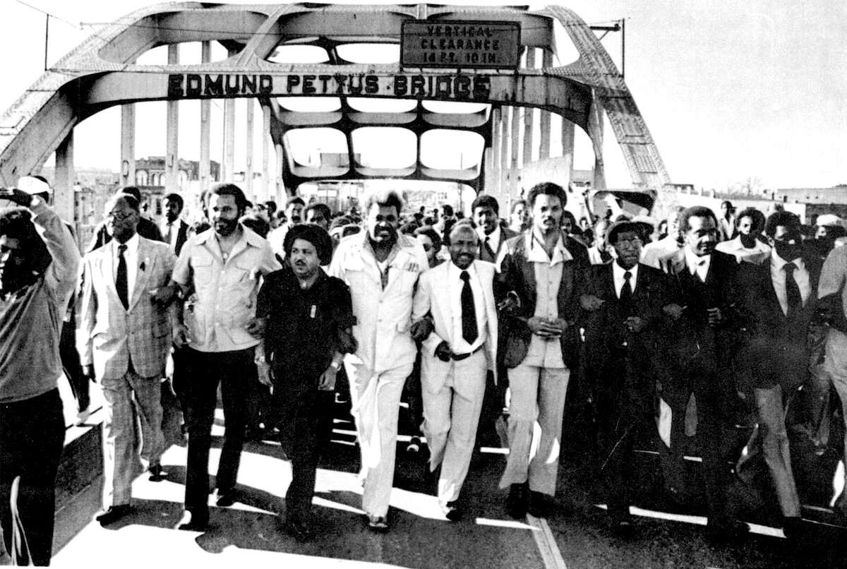 Selma Ala. Voting RIghts March --Marcher s urging Congress to extend the U.S. Voting Rights Act walk arm -in-arm across the Edmund Pettus Bridge in Selma Ala., on Sunday, retracing the steps of the 1965 voting rights protests which was turned back by club-swinging state troopers. The march Sunday, with upwards of 5,000 blacks joining in, was peaceful. March leaders included the Rev. Jesse Jackson of Chicage, fourth from right and the Rev.Joseph Lowery of Atlanta, third form right. 1980
