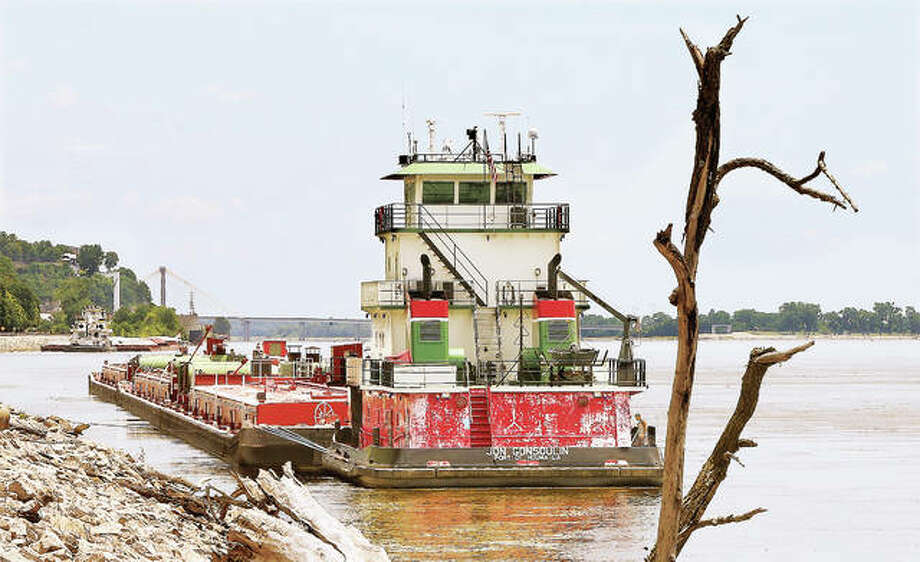 Two of several towboats and their barges sit along the Illinois shore Tuesday just upstream from Alton awaiting their turn to lock through the Melvin Price Locks and Dam 26, following the second of two accidents at the dam this month. The most recent was Monday night involving a tow striking the auxiliary lock and forcing the closure of the dam until Tuesday morning. On July 6, the upstream liftgate of the main, larger lock, was damaged when it was struck by a towboat. Photo:     John Badman | The Telegraph