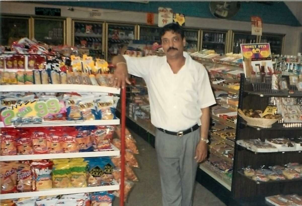 """Hasmukh """"Hash"""" Patel stands inside his convenience store in 1988. He was murdered there in 2004."""