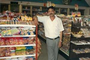 "Hasmukh ""Hash"" Patel stands inside his convenience store in 1988. He was murdered there in 2004."