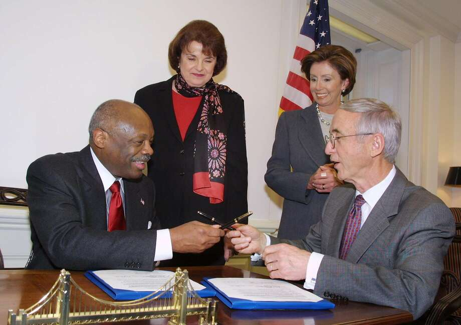 San Francisco Mayor Willie Brown exchanges pens with Navy Secretary Gordon England in Washington after signing an agreement with the Navy for a master plan for the cleanup of hazardous waste at the former Hunters Point Naval Shipyard, as Sen. Dianne Feinstein and Rep. Nancy Pelosi watch on Jan. 23, 2002. Photo: Terry Ashe / Associated Press 2002
