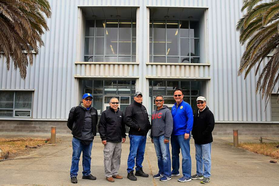 Lewis Fong (left), Richard Tong, Paul Swiatko, Mel Bautista, Mark Madsen and Victor Tsang pose for a reunion photo in May at the Hunters Point Shipyard outside Building 606, where they were stationed when they worked as part of the Tactical Division of the San Francisco Police Department. Photo: Lea Suzuki / The Chronicle