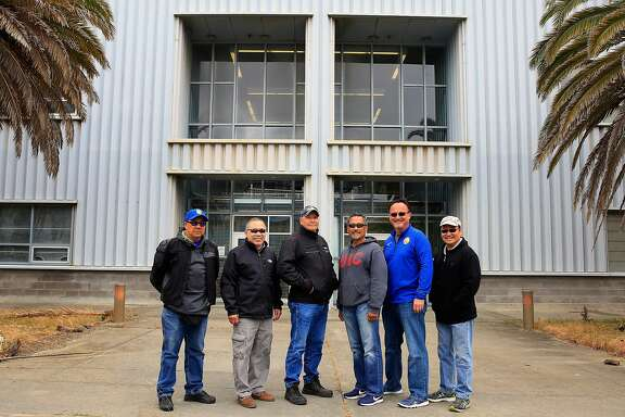 Lewis Fong (left), Richard Tong, Paul Swiatko, Mel Bautista, Mark Madsen and Victor Tsang pose for a reunion photo in May at the Hunters Point Shipyard outside Building 606, where they were stationed when they worked as part of the Tactical Division of the San Francisco Police Department.