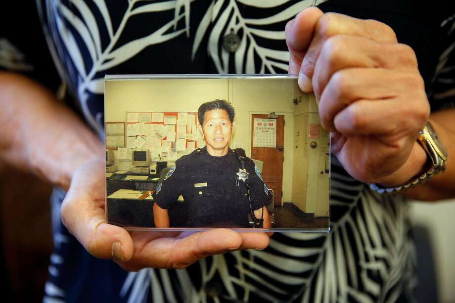 Nelson Lum holds a photo of himself as a San Francisco police officer. Lum, now retired, worked in Building 606 at the former Hunters Point Naval Shipyard, a Superfund cleanup site. Lum and several other officers contracted cancer but are not sure working at Building 606 is linked to the disease. Photo: Santiago Mejia / The Chronicle