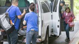 A woman and a child get out of an unmarked van Tuesday  at a Catholic Charities facility where reunited undocumented families are taken after they are released from custody by the Department of Homeland Security.