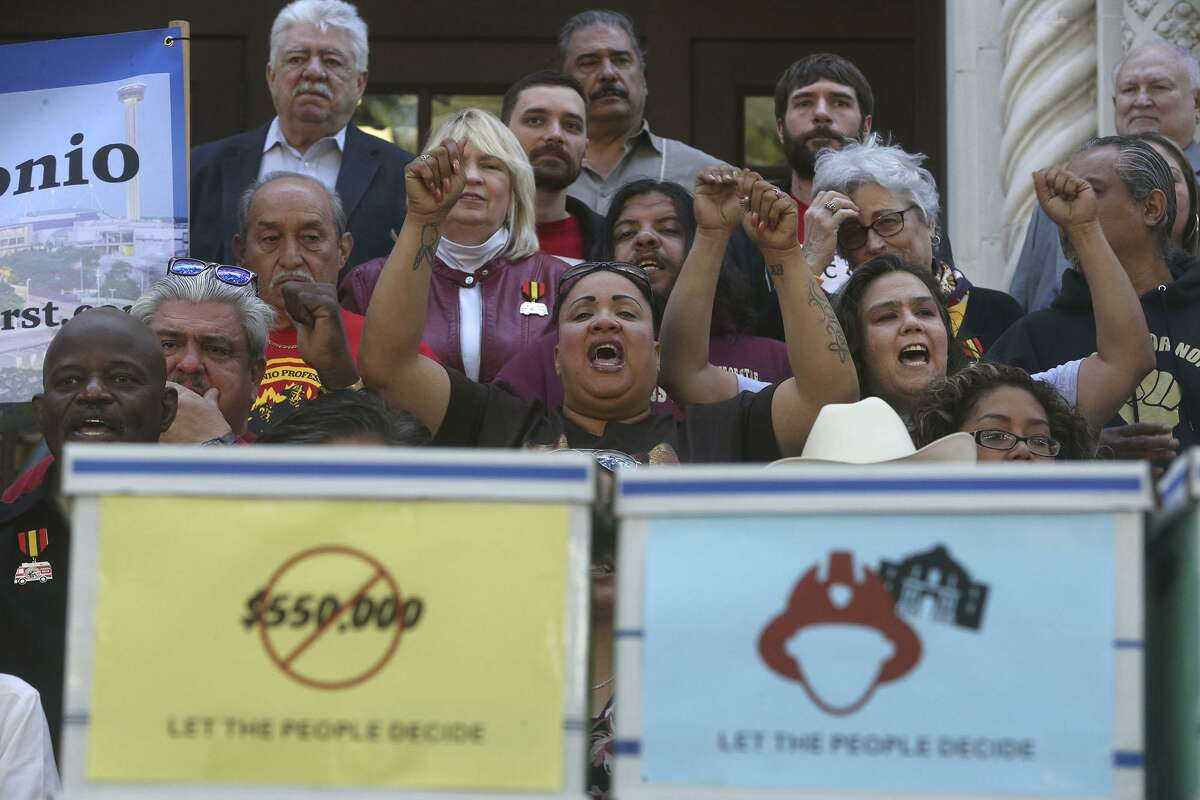 People cheer while Chris Steele, president of the San Antonio firefighters union, speaks Wednesday April 11, 2018 on the steps of City Hall about a petition campaign to call for a city charter amendment election in November. Steele and his supporters delivered thousands of signatures to the city clerk after he and his supporters voiced their opinions outside of city hall.
