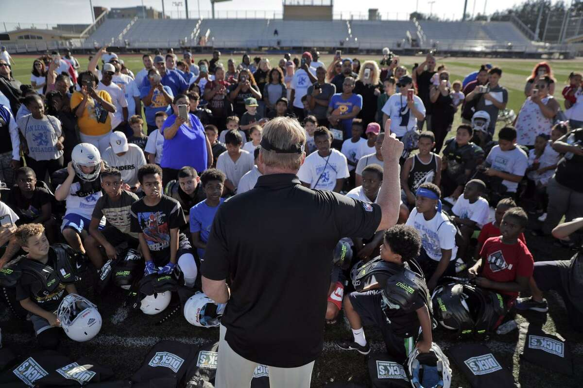 """""""I'm on a mission to encourage kids to play,"""" says Raiders coach Jon Gruden as he meets members of the East Bay Panthers and San Leandro Crusaders at Burrell Field in San Leandro."""